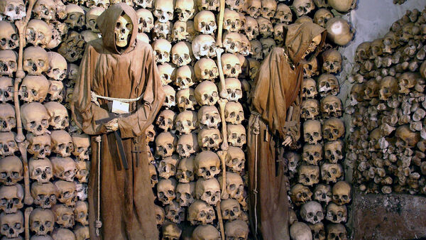 Neatly stacked skulls and robed monk skeletons in the Capuchin Crypt of Rome