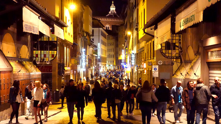 """People strolling the narrow pedestrian streets of Florence during its nightly """"passeggiata"""""""